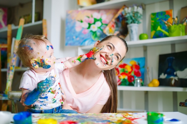 Mom and daughter paint on canvas at the drawing school. Premium Photo
