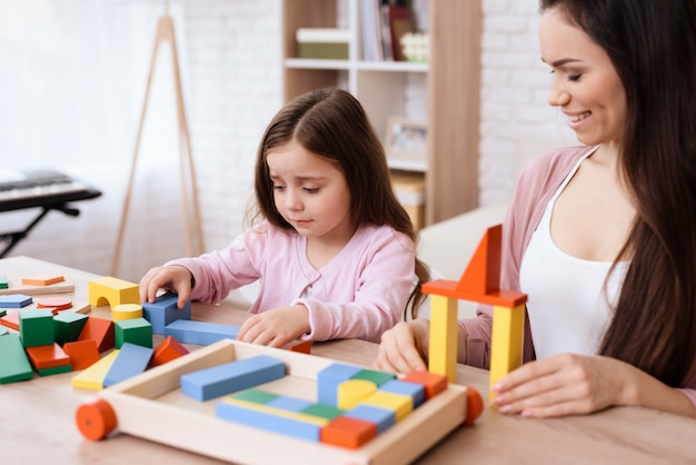 Mom and daughter play together with wooden cubes. Premium Photo