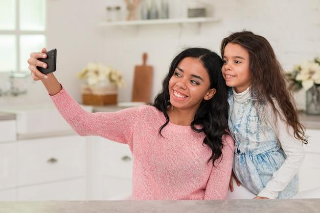 Mamma e figlia prendendo selfie Foto Gratuite