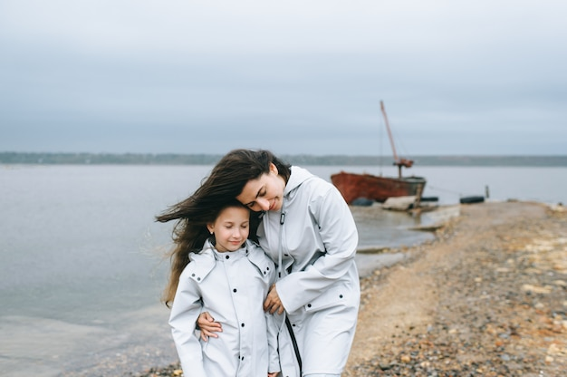 Mom and dauther  have a fun on a boat background near the lake Premium Photo