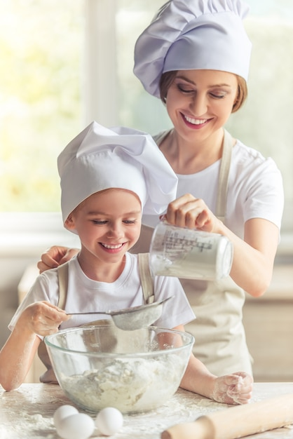 Mom and girl are smiling while preparing the dough Premium Photo