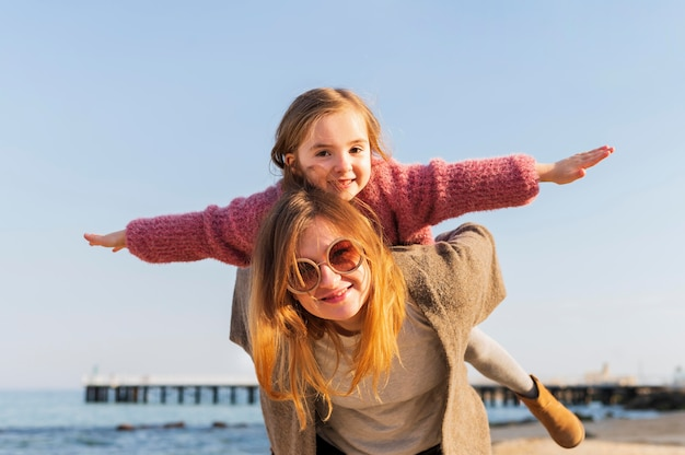 Mom giving piggyback ride front view Free Photo