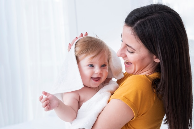 Mom holding baby with towel Free Photo