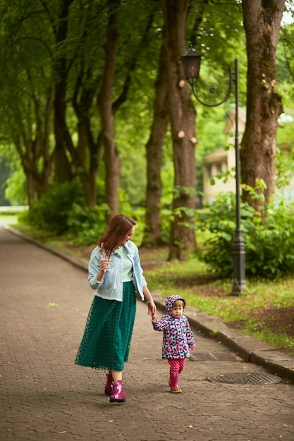Mom holds daughter's hand walking with her in the park after rain Free Photo