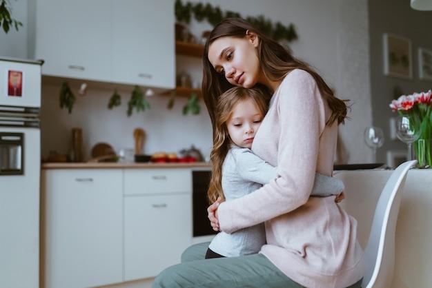 ママは台所で娘を抱きしめ、両方の顔は静かな悲しみまたは悲しみの表現を持っています Premium写真
