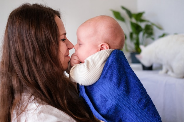 Mom hugs her little cutest baby after bath with blue towel on head. infant child on mother hands. mothercare love. family life. mother and baby. happy motherhood Premium Photo