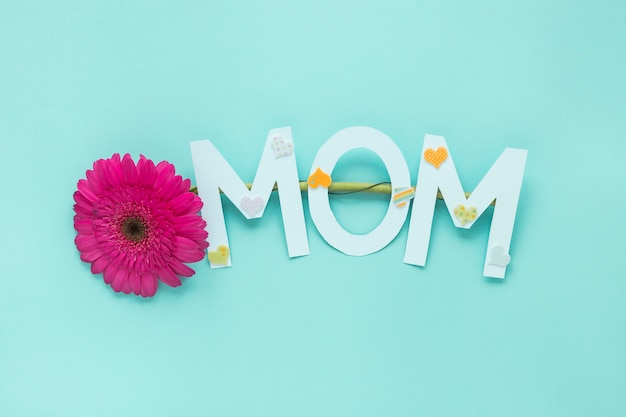 Mom inscription with gerbera flower on table Free Photo