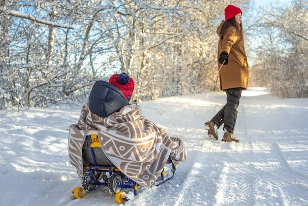 凍るような冬の晴れた日を戸外で歩いているそりでお母さんが子供を引っ張っている Premium写真