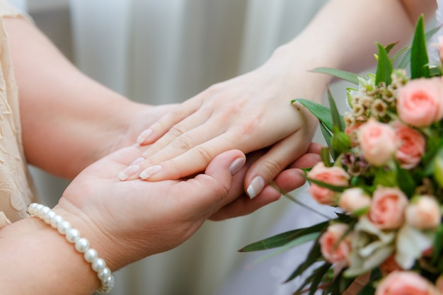 Mom keeps her daughter by the hand on the wedding day. Premium Photo