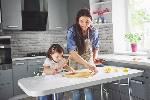 クッキーの娘のためにオーブンを愛するママ。 無料写真