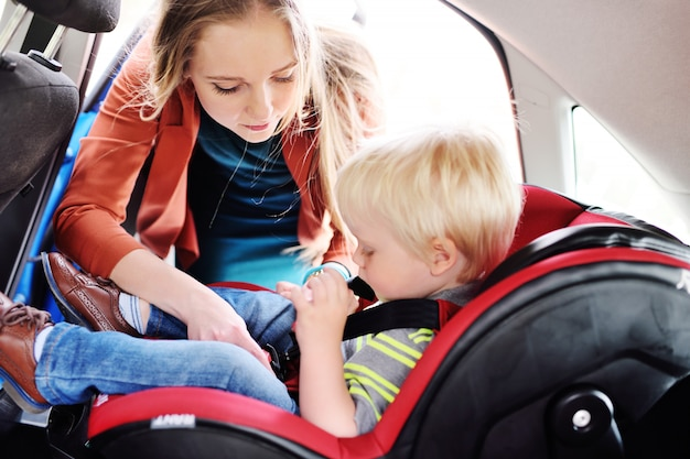Mom puts the child in the car seat and fasten seat belts. Premium Photo