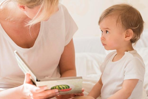 Mamma che legge al bambino nel letto Foto Gratuite