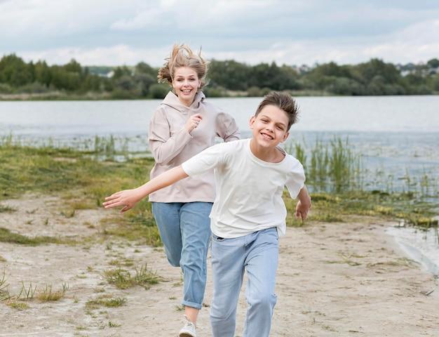 Mamma che corre con suo figlio sulla sabbia Foto Gratuite