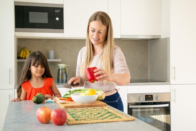ママが娘に夕食にサラダを作る方法を示しています。少女と彼女の母親は台所のカウンターで野菜を切る。ミディアムショット、コピースペース。家族の料理のコンセプト 無料写真