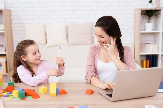 お母さんは娘の隣に座って電話で話します。 Premium写真
