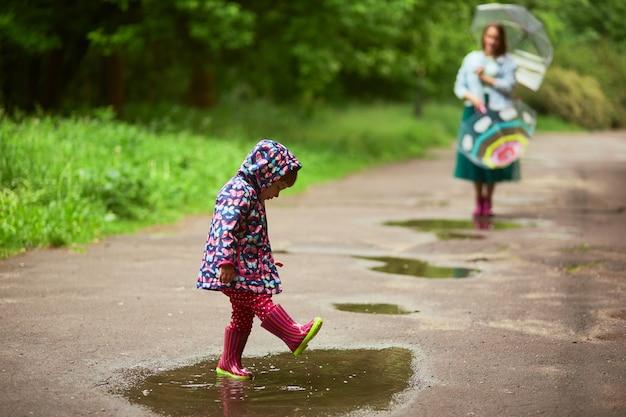 雨の後に娘がプールで遊んでいる間に、ママは傘で背後に立つ 無料写真