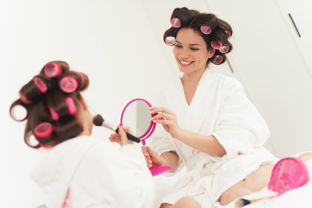 Mom teaches a little daughter to do makeup Premium Photo