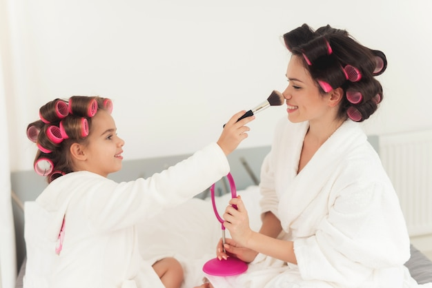 Mom teaches a little daughter to do makeup. Premium Photo