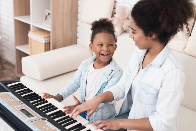 Mom teaches a little girl to play the piano. Premium Photo
