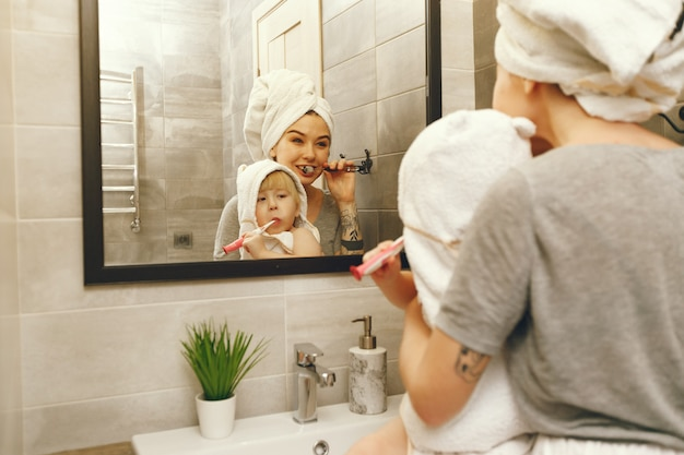 Mom teaches little son to brush his teeth Free Photo