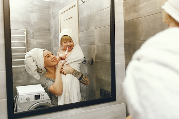 Mom teaches little son to brush his teeth Free Photo