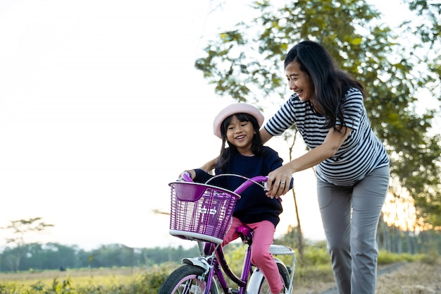 Mom teaching her toddler daughter to learn bicycle Premium Photo