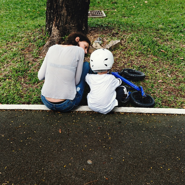 Mom teaching son how to ride a bicycle outdoors Free Photo