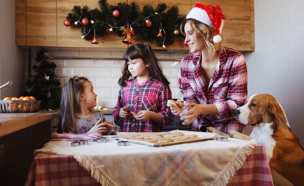 ママは娘たちと愛犬と一緒にジンジャークッキーを用意し、キッチンで楽しんでいます。クリスマスの準備。家族の伝統。 Premium写真