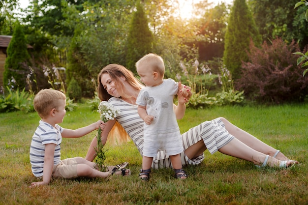 Mom, two children rest on nature. sibling rivalry. brothers, motherhood. Premium Photo