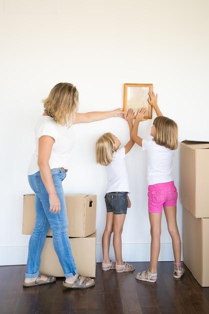 Mamma e due ragazze che appendono cornice in bianco sulla parete bianca Foto Gratuite