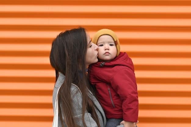 Мама с младенцем на руках в теплой одежде, на оранжевом фоне. Premium Фотографии