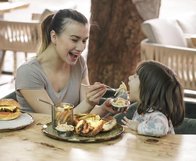 카페에서 패스트 푸드를 먹는 귀여운 딸과 엄마 무료 사진