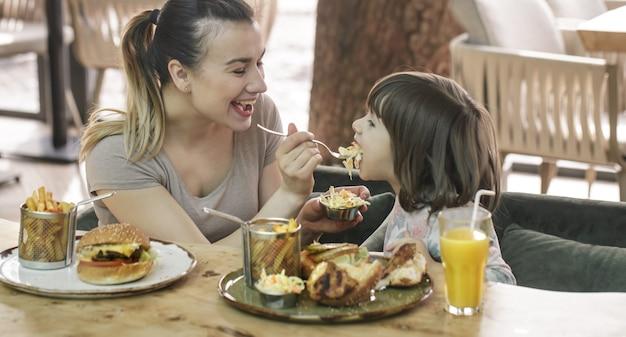 カフェでファーストフードを食べるかわいい娘とママ 無料写真
