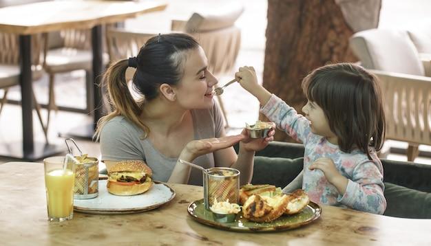 Мама с милой дочерью едят фаст-фуд в кафе Бесплатные Фотографии