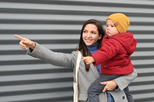 Мама с младенцем на сером Premium Фотографии