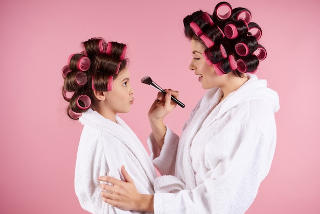 Mom with a brush in her hands does makeup to a little girl Premium Photo