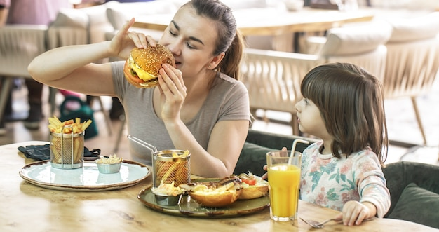 Mom with a cute daughter eating fast food in a cafe Free Photo