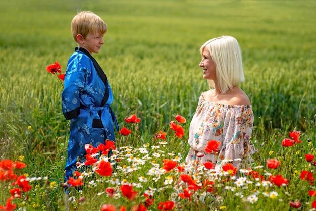 壮大な草原で息子とお母さん。その少年は母親を赤いケシで驚かせた Premium写真