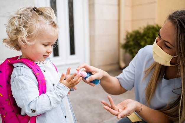 Mom with medical mask spraying child's hands with sanitizer Premium Photo