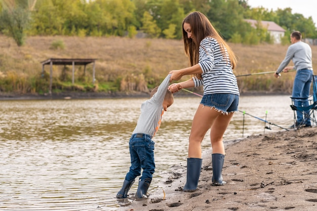 Mom with a small son walks along the sandy shore of the lake in rubber boots. hanging out with children in nature, away from the city Premium Photo