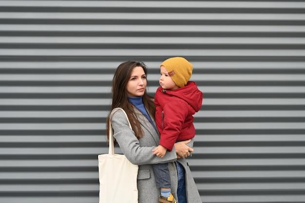 Мама с мальчиком малыша на сером Premium Фотографии