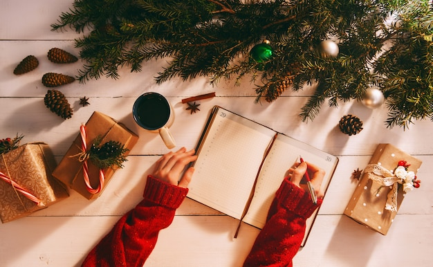 Mom writes to notebook and to-do list of gifts for christmas and new year Premium Photo