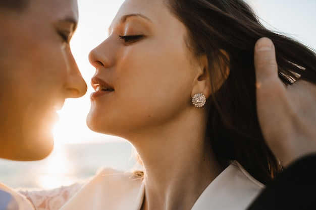 A moment before kiss of a young beautiful caucasian couple on the sunny day outdoors Free Photo