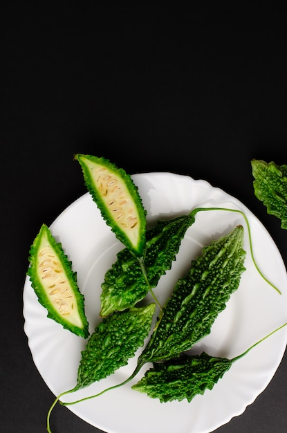 Momordica charanita or bitter cucumber on white plate on black background Premium Photo