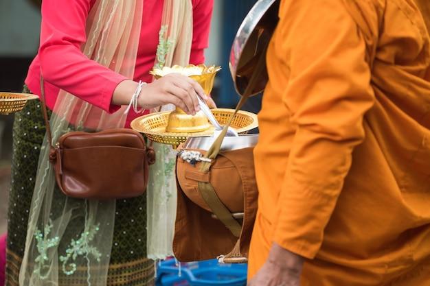 Женщины и посетители деревни мон в традиционной одежде предлагают еду чаше для подаяний буддийского монаха рано утром в районе сангхлабури, канчанабури, таиланд. известная туристическая деятельность. Premium Фотографии