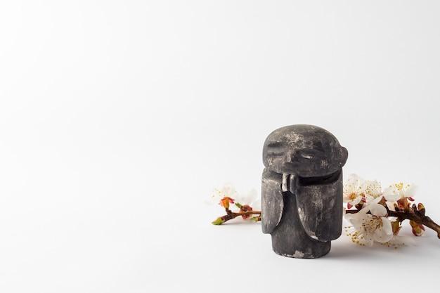 僧monの置物と花のある桜の枝。春と旧正月の概念。 Premium写真