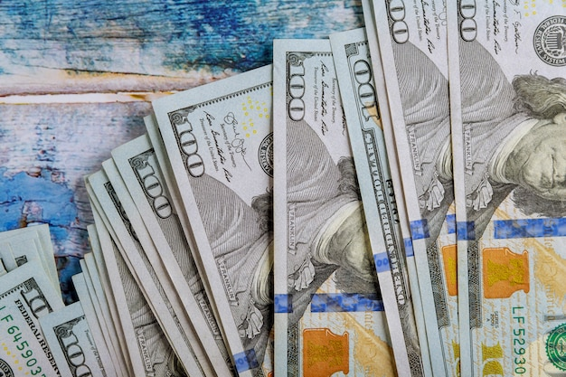 Money american hundred dollar bills in the blue old wooden background Premium Photo