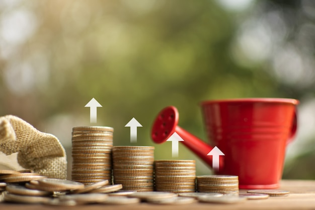 Money bag and coins arranged vertically , saving and growing business concept. Premium Photo