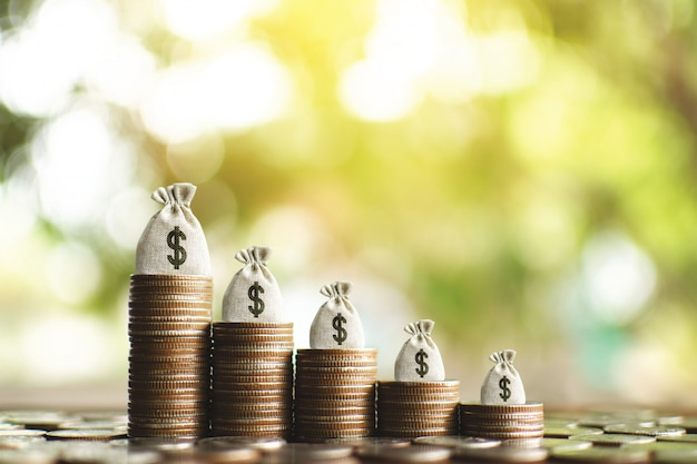 The money bag with a coins on wood plank and tree bokeh background ,start to plan saving for business and lifestyle  . Premium Photo