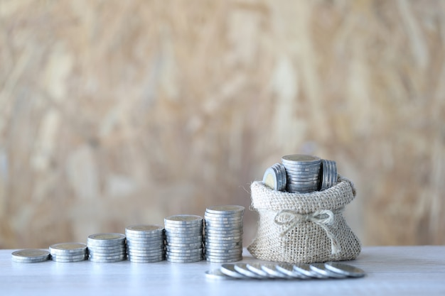 Money bag with stack of coins money on wooder background Premium Photo